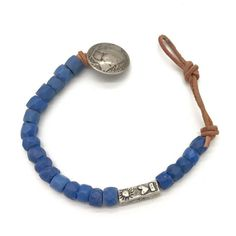"<p>Blue glass beads on natural leather with a rectangular sterling silver bead. Bracelet measures 7 1/2- 8 1/2"". Buffalo closure.</p>"