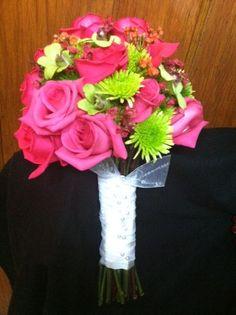 Fresh handheld bouquet of hot princess roses, green dendrobiums, orange waxfower, green kermit poms