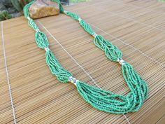 colar comprido de miçangas verde e tubinhos de ceramica pintada usadas como entremeio.