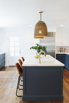 Open kitchen with woven pendant lights, leather barstools, and blue cabinents
