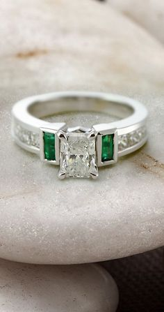 https://www.bkgjewelry.com/ruby-rings/120-18k-yellow-gold-diamond-ruby-ring.html Parallel Grid Ring || Radiant Cut Diamond Side Stone Ring With Green Emerald In 14K White Gold