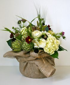 rustic arrangement of hydrangea, grasses, white peony, scabiosa pods, artichoke, scabiosa and cosmos in burlap wrapped vase