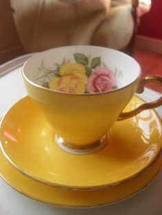Yellow tea cup and saucer with roses inside cup