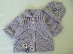 This warm and soft set is hand knitted with double thread of acrilyc yarn. It is specially for cold days. The color is lilac and has pink buttons and crocheted flowers READY TO SHIP The size approx. is 1 to 5 months Sweater -Length: 27cm.- 10.50 inch. -Circumference under arms: 46cm.- 18 inch. -Sleeves unfolded: 19cm.- 7.50 inch. Hat -Circumference unstretched: 34cm.- 13.30 inch. -Length unfolded: 18cm.- 7 inch. Can be machine was in cold water, don´t iron Created in my free smoke home. T...