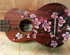 Main peinte de fleurs de cerisier sur votre ukulélé
