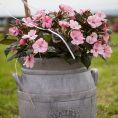 Objects from the farm were used as decorations for Alison and Edward's country-themed wedding. Outside of the reception, dairy canisters were used as planters for pink flowers. Image Credit: Charlene Morton