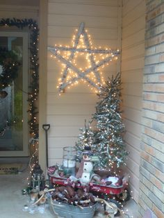"""Christmas decorations on the porch.  Used my old red wagon to house two small lighted Christmas trees, a snowman, and lantern with """"fake"""" candles.  Another lantern sits on the ground along with a vintage silver tub filled with pine cones.  A larger lighted tree stands behind the wagon.  Finally a large star hangs above everything.  Fake snow adds a greater holiday feel."""