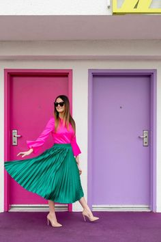 Jennifer Lake Style Charade in a green satin pleated skirt, pink bell sleeve top, Cult Gaia bag, and Steve Madden pumps at the Saguaro Palm Springs colorful doors Satin Pleated Skirt, Green Pleated Skirt, Pleated Skirt Outfit, Skirt Mini, Stripe Skirt, Skirt Outfits, Turquoise Skirt, Moda Formal, Color Turquesa