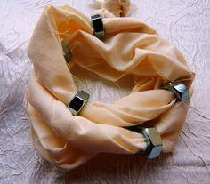 Bransoletka z nakrętkami, na mocnej tkaninie specjalnie poszarpanej. Bransoletka zawijana i wsuwana na rękę. Można również nosić jako naszyjnik.