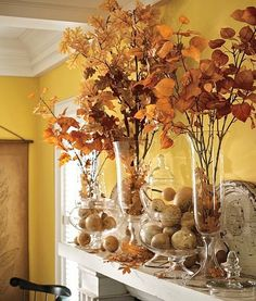 Glass vases with mini pumpkins and fall leaf branches.