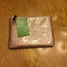 NWT, Kate Spade Mini Pouch, sparkling rose gold  Brand new with tags, can carry money in pouch or others items in this. Has two slots that cards could go in and cell phone will fit! Great stocking stuffers i phone 6 will fit!  Great for party to carry lip stick!  Price is firm! No trades! kate spade Bags Clutches & Wristlets