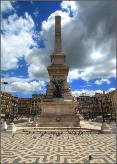 Praça dos Restauradores, stadsdeel Baixa, Lisboa. Hoog oprijzende obelisk die er in 1886 werd neergezet ter ere van de Restauratie (de bevrijding van het Spaanse juk) in 1640. De bronzen figuren op het voetstuk die een palm en een kroon vasthouden, beelden Victorie en Vrijheid uit
