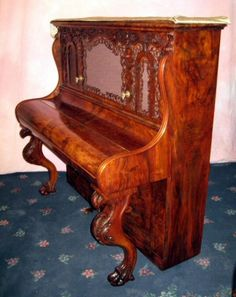 Antique Pianos- This circa 1850 cottage piano also features and Chippendale-style legs with highly carved knees and clawed feet.