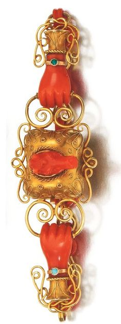 GOLD AND CORAL BRACELET, EARLY 19TH CENTURY Set with a carved coral horse's head within a gold surround, held by carved coral hands accented with small turquoise cuffs, backed by alternating coral and gold links, length approximately 185mm.