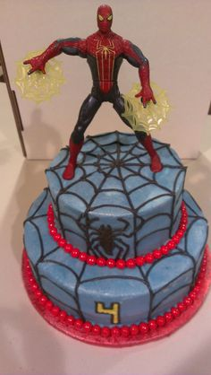 Spiderman cake.  figurine on the top.  buttercream decorations, red round candies around base