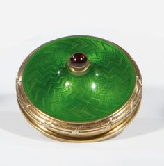 A silver-gilt and guilloché enamel bell-push. Circular form, cabochon button, the surface with green translucent enamel over engine-turning. Bearing spurious Russian hallmarks. 2nd half 20th century. Diam. 6.8 cm.