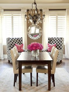 plantation shutters. white floor length drapes. geometric print chairs. bright pink arge flowers.