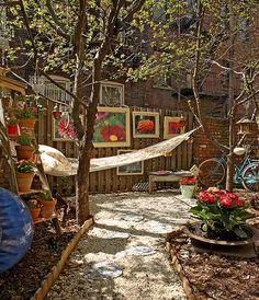 O duplex da designer de interiores Barbara Saulzman tem até jardim. Aqui, o caminho de pedriscos leva à rede com almofadas. Presos à cerca de madeira estão quadros feitos com molduras antigas e fotografias de flores