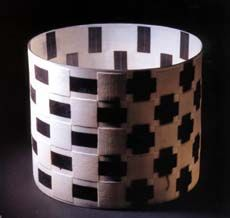 Cylinder with Blue-Black lines by Danish ceramicist Bodil Manz (1943-  ), a master of eggshell porcelain. Her slip cast porcelain cylinders are decorated with geometrical patterns on both sides, so the pattern on one side, is offset by the shadow of a related pattern on the other. Interior and exterior play off one another. Manz also designs tea and dinner sets and has large scale architectural pieces.