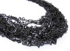 """Akiko Kurihara - < 1000g >, necklace, material: silver925. This neckpiece is about 15 meters in total length. It consists of a 1000 similar characters, the """"g"""". Each """"g"""" weights exactly 1g(gram). The total weight of the necklace is thus 1kg. Of course, the character """"g"""" denotes a unit of weight, but somehow the shape itself looks like a piece from the chain too. By trying this piece on, you realize how heavy 1kg(1000g) is."""