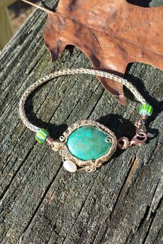 This bracelet contains a blue-green dyed magnesite gem, simulated turquoise. It is surrounded by a gold colored wire woven bezel with swirls and a freshwater pearl. The band of the bracelet is handmade Viking knit, with glass bead end caps and a copper clasp. The copper is a mix of non-tarnish and naturally antiquing. The Viking knit, made of tarnish resistant gold colored copper wire, has a core of black cord to give more contrast. The total length is about 8.25 inches. If you would like to…