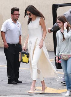 Kendall Jenner worked her longline slitted sweater with cream high-waisted pants, neutral pumps, and a gold watch. She chose a colorblock tricolor Céline bag as her statement accessory.                  Source: FameFlynet