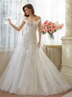 Sophia Tolli Y11635 Vasya Wedding Dress - This Parisian inspired Sophia Tolli Y11635 Vasya tulle wedding dress really ups the elegance factor. Its round scoop neckline gives way to wide straps that sit off the shoulders while a small plunge sits beneath a sheer overlay. Lace applique is scattered over gathered tulle creating a gorgeously full A-line skirt. The real piece de resistance is the back, with a large keyhole cutout and corset lacing to fasten it up. A long chapel train is a…