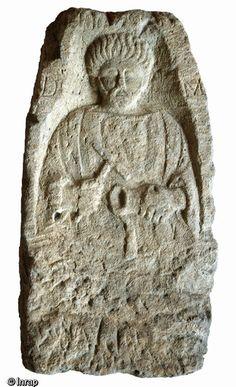 Stèle funéraire gallo-romain en arkose (hauteur 79 cm, largeur 25 cm), première moitié du IIe s. de notre ère, nécropole de Pont-l'Évêque,..ce personnage est un artisan du métal, peut-être un dinandier: il tient un marteau et un gobelet dont le rebord est placé sur un support posé d'équerre. Son nom est illisible. 2 lettres seulement apparaissent, de part et d'autre du personnage: D et M (aux dieux mânes).