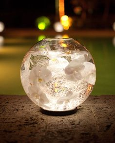 Glass globes filled with water, silver thread and orchid heads are placed on LED light coasters. Great centerpiece for evening wedding.