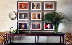 Above a long 19th-century fruitwood console table hangs a series of artworks by Breon O'Casey (breon-ocasey.co.uk). The shell sconces are  by Porta Romana (portaromana.co.uk)