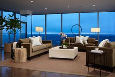 A penthouse living room has polished concrete floors and dramatic views of Lake Michigan in the distance.