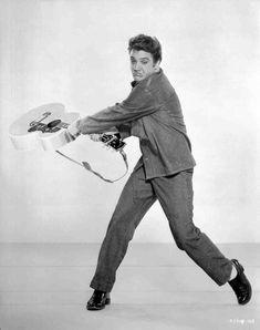 Full shot of Elvis Presley as Vince Everett making face and swinging guitar.