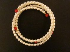 """This shimmering pearl coil bracelet has 107 rice-shaped cultured freshwater pearls accented with coral and 14k gold beads. Most of these coil bracelets have only 2 loops of pearls, but this one has 3 loops on sterling silver """"memory"""" wire which holds the pearls in a beautiful coil that fits any wrist. A huge bargain at $19.99 FREE SHIPPING"""