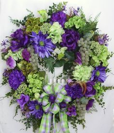 """This beautiful Spring, Summer Grape door wreath sets on a nature grapevine wreath base.  The wreath is embellished with lots of fern Greenery, purple Roses, Mums, light green and green Hydrangea, and light purple/purple Gerbera Daisies. The wreath is accented with three clusters of green grapes and a cut purple bird. I finish the wreath with a light green/purple checker Ribbon Bow and a purple Ribbon Bow.  The wreath measures from tip to tip at 27"""" (L) x 26"""" (W) x 7""""(D)."""