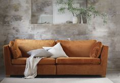 We love this juxtaposing set up, the limewashed walls and concrete floors juxtapose the glamorous cognac velvet sofa | The midcentury style sofa makes a strong style statement agains the rustic backdrop | seen here: an IKEA Stockholm sofa with a Bemz cover in Cognac Simply Velvet
