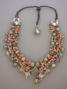 by Moroccan Designer Fouzi | Necklace; Antique coral shell money from Mauritania and beads from the High Atlas Mountains that are80 - 120 years old. The central square pendant is from Tazenakht in theOuarzazate Province of Morocco.  Tambashells from Africa - very rare and sought after. The silver pendants areincredibly hard to find - Jewish pieces from Essaouria, circa 1920. It tooka lifetime of collecting to create a graduated set as exquisite as this one. | 4'495$