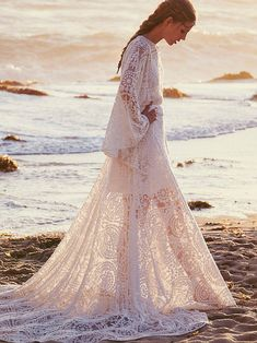 Lady Wren Gown | Completely ethereal and goddess-like, the style's intricately embroidered sheer mesh lace, flowing hemline, and dramatic dolman sleeves add to its majesty. For the romantic bohemian on her wedding day, she's radiant against sandy scape with soft waves crushing in the distance. Gathers at the waist with adjustable tie belt. Upper back keyhole with gemstone closure. A sheer and illusory style, with a strappy silk knee-length slip included. Imagine wind-swept hair and sea…