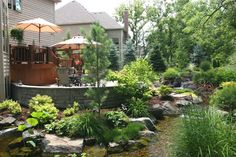 Multi-layer deck overlooking beautiful garden and water feature, from Aquascape Your Landscape. Forget the lawn mower.