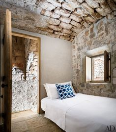 The bed in the monastic guest room is topped with a Madeline Weinrib ikat pillow.