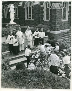BICYCLES ALSO RECEIVE BLESSING Baldwin, L. I. --- Mass section of bicycles being blessed by the Rev Ulick O'Sullivan Buckley assisted by Rev. Francis J. Burns in honor of St. Christopher, patron saint of travelers. The scene is before St. Christopher's R.C. Church at Balwin, Long Island. Credit Line ACME: 7-25-39
