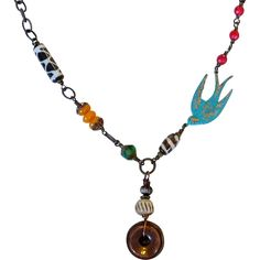 Safari Inspired Asymmetrical Bird Necklace Did you know that sparrows symbolize hope, love, safety, protection, fertility and creativity? A large antique bronze verdigris patina finish sparrow pendant that measures 40x18mm and has a gorgeous aged green look from the patina finish. Exotic Amber, Giraffe Print, howlite, and czech glass complete the asymmetrical chain and is finished with a hook clasp. A bronze chain with drops of bone and bronze sway below.