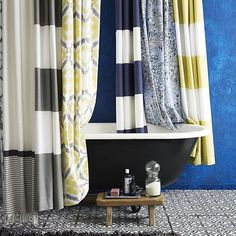Washroom, striped & patterned shower curtains, black tub, tiled floor, claw foot tub