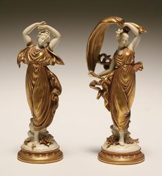 German porcelain classical female figures; draped muses in gilt attire on circular bases with applied flora. 10 1/4H.