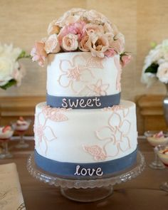 Sweet words and fresh flowers embellish this two-tiered cake