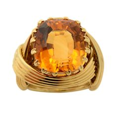 SCHLUMBERGER. A large citrine stone is cradled in bands of crisscrossed gold in this strongly designed ring by Schlumberger. Circa 1980s