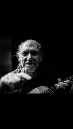 Take this shot in the middle of the night, homeles guy playing the gituar.