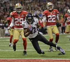 Baltimore Ravens wide receiver Jacoby Jones (12) crosses the goal line to score a 56-yard touchdown against San Francisco 49ers defensive back Chris Culliver (29) and cornerback Carlos Rogers (22) in the second quarter of the NFL Super Bowl XLVII football game, Sunday, Feb. 3, 2013, in New Orleans. (AP Photo/Dave Martin)