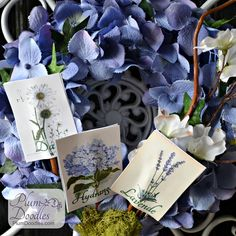 Spring Wreath Tutorial - coat hanger, fabric, hydrangea blooms, seed packets (she printed images from The Graphics Fairy) & glue.