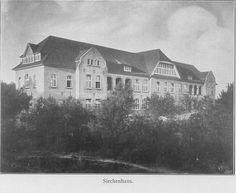 Schwarz-Weiß-Foto: großes dreistöckiges Haus mit vielen Bäumen im Vordergrund