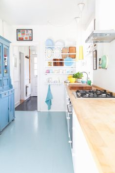 pale aqua painted floor looks good in this white kitchen with light butcher block counter tops. home decor and interior decorating ideas. Rustic Kitchen, New Kitchen, Kitchen Decor, Kitchen Design, Stylish Kitchen, Kitchen Units, Kitchen Paint, Painted Wooden Floors, Sweet Home